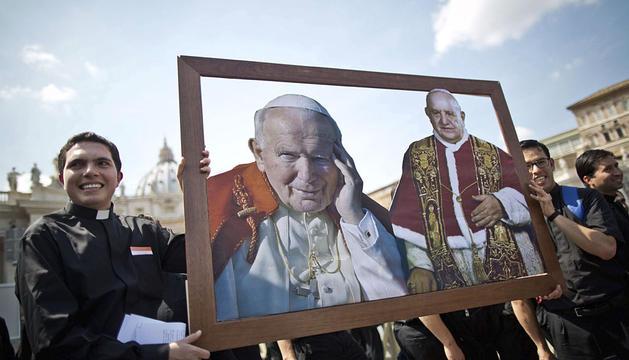 Dos jóvenes sacerdotes sostienen una imagen del papa Juan Pablo II y Juan XXIII.