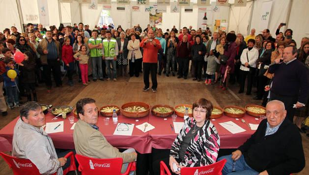 Los componentes del jurado, Santiago Cordón, Juan Gimeno, Blanca Rodríguez e Ignacio Ramírez, con las menestras que se presentaron al concurso y el público al fondo.