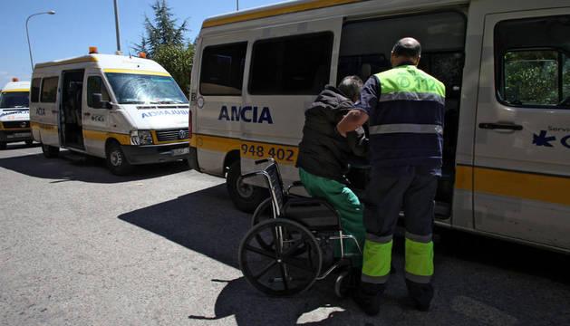 Un trabajador de las ambulancias ayuda a un paciente a subir al vehículo en el Reina Sofía de Tudela.