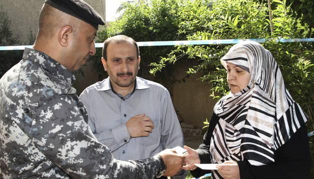 Un policía iraquí pide la documentación a una pareja que acude al coelgio electoral para ejercer su derecho al voto en Bagdad (Irak).