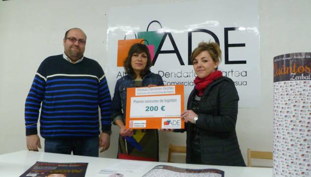 La diseñadora del logo, Elena Vera, recibe el premio de Estíbaliz Asensio ante Alberto Anguiano. Cedida