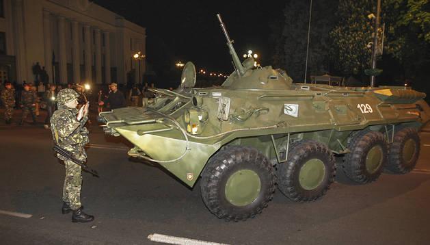 Un soldado ucraniano ayuda a sus compañeros a aparcar un tanque durante una maniobra cerca del Parlamento en Kiev