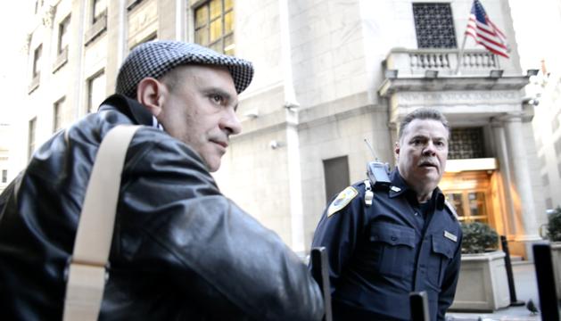 Arturo Cisneros, a la izda, junto a un policía de la Bolsa de Nueva York