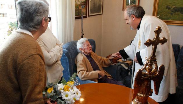 María Pascual y Jesús Sótil se saludan junto a la imagen del Ángel de Aralar, en la visita de abril de 2013