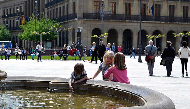 Unos niños juegan con agua en la Plaza del Castillo