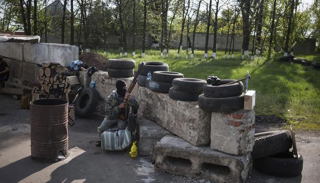-Un activista prorruso armado hace guardia en un improvisado puesto de control en Slaviansk.