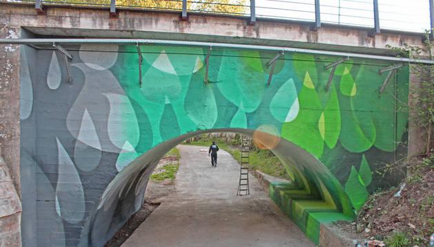 Aspecto del puente, uno de cuyos arcos se ha ilustrado con un 'graffiti' que combina verdes y azules en grandes gotas de agua.