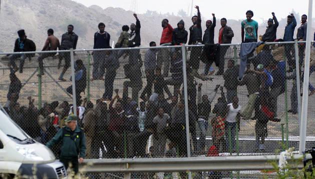 Inmigrantes subsaharianos encaramados a la valla de Melilla