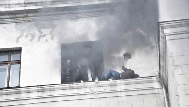 Activistas prorrusos tratan de escapar por una ventana del incendio en la Casa de los Sindicatos de Odessa