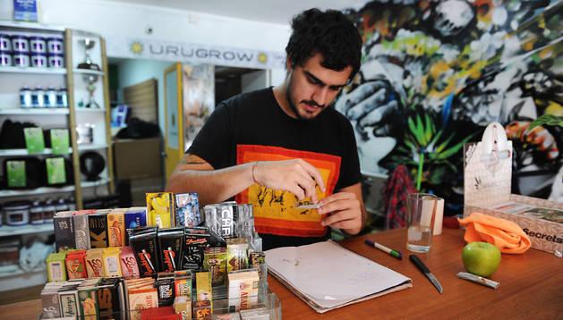 Juan Manuel prepara un porro de marihuana en su negocio de Montevideo