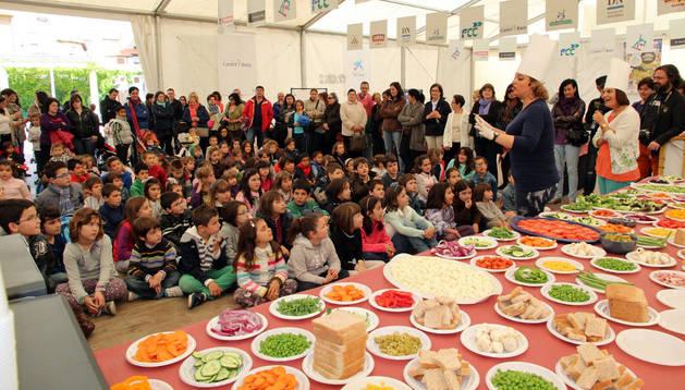 Varios niños, con los ojos tapados, palpan las verduras colocadas ante ellos durante el taller 'Verduras en la Oscuridad'.