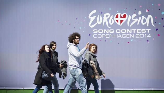 Gente caminando frente al carte promocional del Festival de Eurovisión en Copenhague. EFE