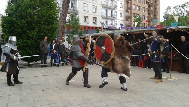 Los integrantes de la Orden de la Jarra representan un combate medieval, a la entrada del parque municipal de Burlada, ante la mirada de decenas de personas