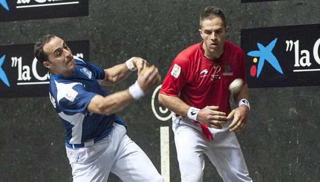 El pelotari Juan Martínez de Irujo (i) golpea la pelota junto a Aimar Olaizola (d) durante la final del Campeonato de Parejas 2014 .