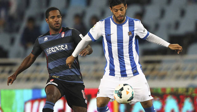 Carlos Vela cubre el esférico ante la presión del jugador del Granada Allan Nyom