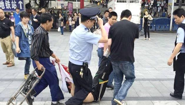 Un policía y varias personas arrastran a un sospechoso