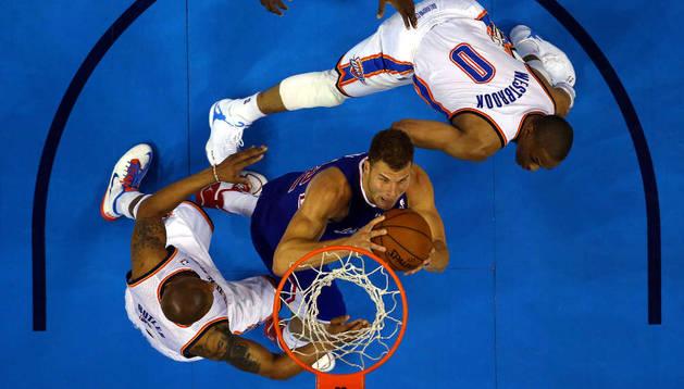 Blake Griffin, jugador de los Clippers, tira ante Caron Butler y Russell Westbrook