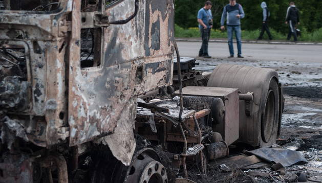 Residentes caminan junto a los restos de un camión incendiado después de un tiroteo en Slaviansk