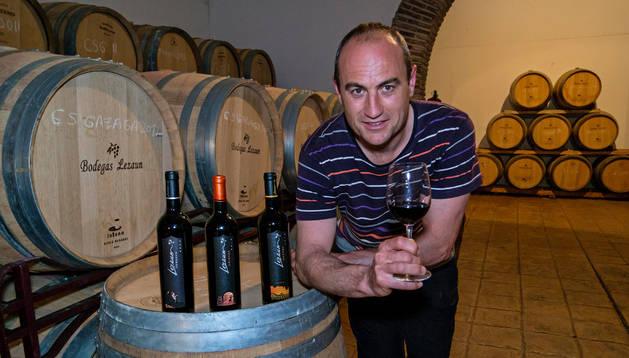 Raúl Lezaun Etxalar sujeta una copa y se apoya en una barrica con tres botellas dentro de su bodega.