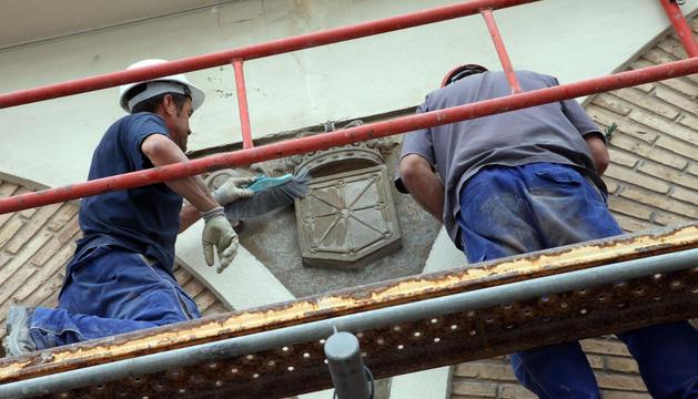 Dos operarios proceden a eliminar la laureada del escudo de Navarra.