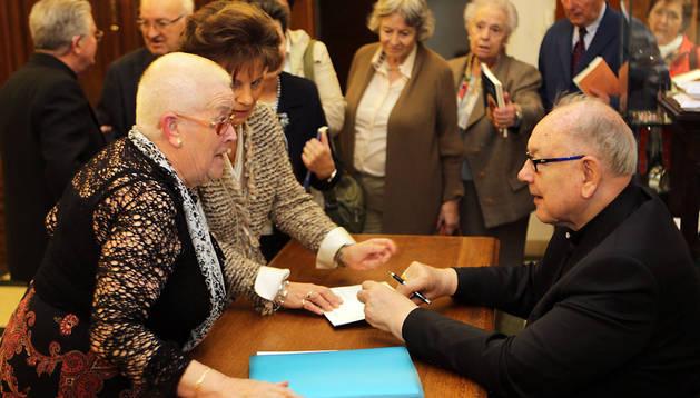 Un grupo de personas rodea a Fernando Sebastián durante la firma de un libro suyo en la parroquia de San Miguel.