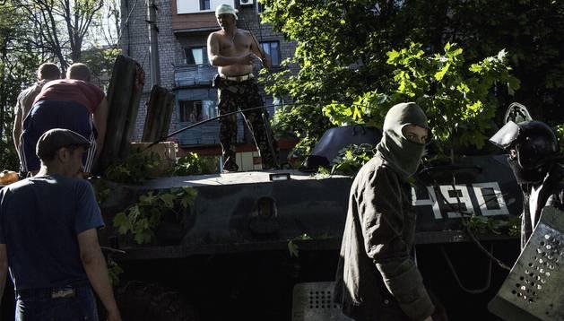 Los activistas prorrusos guardan un tanque de Ucrania en Mariupol.