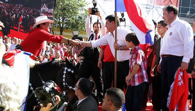 El presidente paraguayo, Horacio Cartes (c), electo en abril de 2013, saluda a un jinete del Partido Colorado