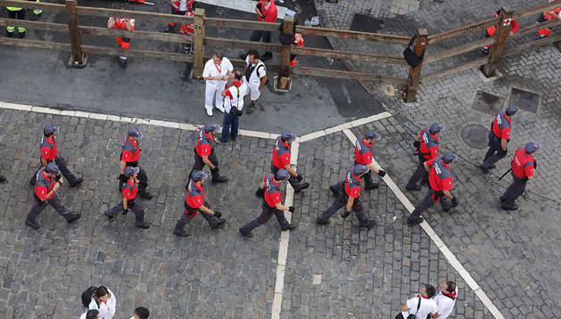 Agentes de la Policía Foral inspeccionan el recorrido en el tramo de Telefónica antes de que comience el último encierro de las fiestas de San Fermín del pasado año