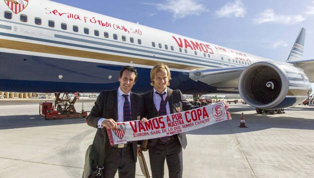 Iván Rakitic y Unai Emery posan con la bufanda conmemorativa ante el avión del equipo momentos antes de embarcar