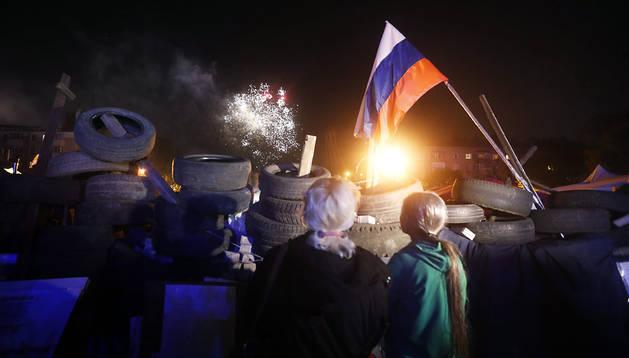 Un grupo de personas observa fuegos artificiales durante la celebración del anuncio de los resultados del referendo