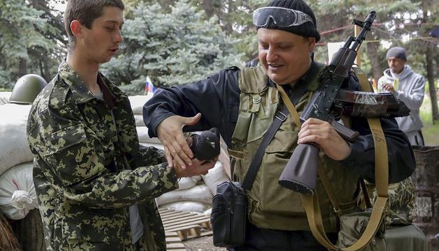 Prorrusos armados toman una paloma como mascota en una barricada levantada en Lugansk.