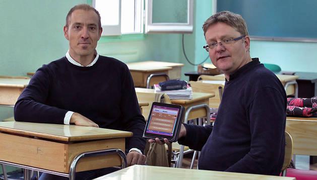 Los profesores de Carmelitas Vedruna Luis Villanueva y Al Macaulay enseñan en un tablet la aplicación que han diseñado para aprender los 'phrasal verbs' de inglés en una de las aula del colegio pamplonés