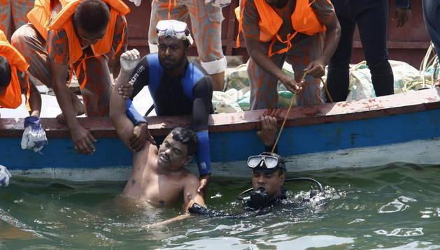 Miembros de los servicios de rescate sacan del agua uno de los cadáveres tras el naufragio del barco MV Miraj 4 en el río Megna cerca de Munshiganj (Bangladesh)