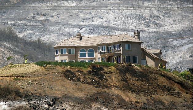 Varios bomberos rodean una casa que se ha salvado de las llamas en San Marcos, California