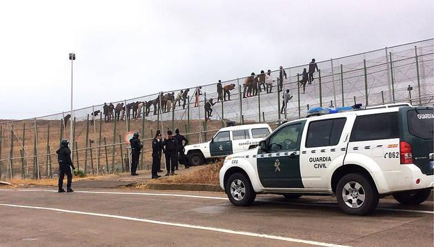 Varios inmigrantes, encaramados en la valla de Melilla
