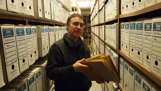 En el archivo Carlos Maiza Ozcoidi, que ha afrontado la última fase de ordenación del archivo municipal, rodeado por cajas de documentos.