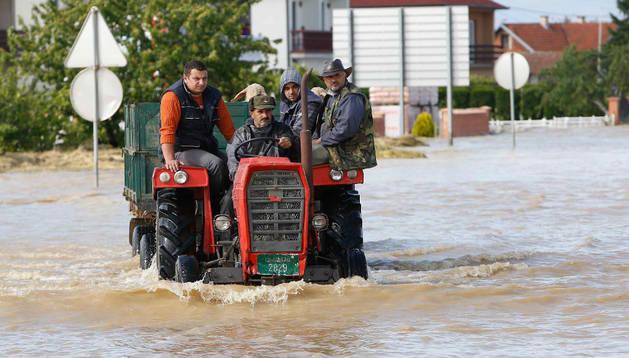 Bosnios sobre un tractor en una calle inundada en el este de Bosnia. AFP