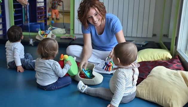 Una educadora juega con tres bebés en una de las aulas de lactantes de la escuela infantil Hello Rochapea