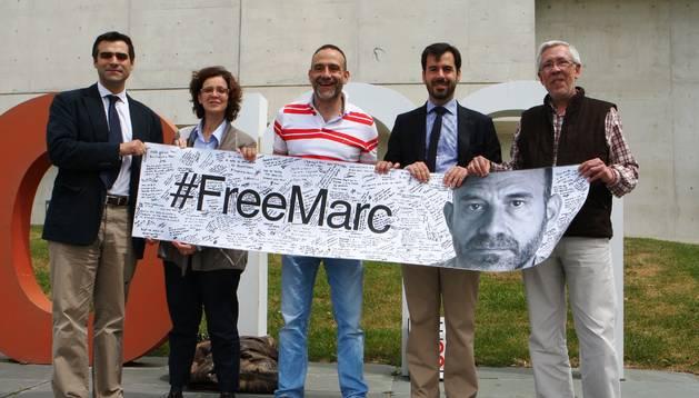 Marc Marginedas, en el centro, posa con la pancarta firmada.
