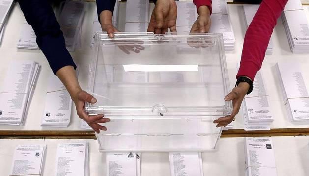 Tres personas sujetan una urna sobre las papeletas en un colegio electoral de Pamplona