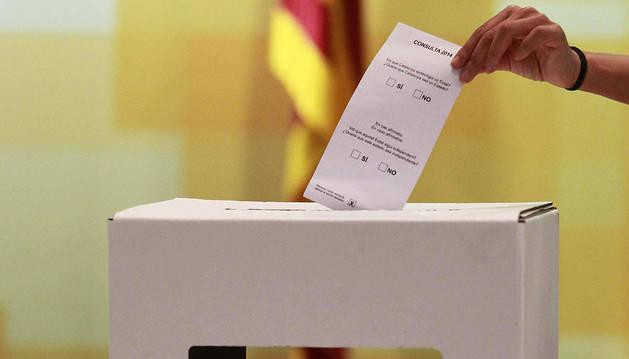 Una persona introduce una papeleta con las preguntas en el modelo de urna elegida para la consulta popular catalana