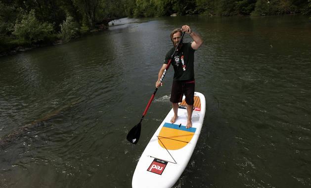 El aventurero navarro Telmo Aldaz rema sobre una tabla de paddle surf por el río Arga