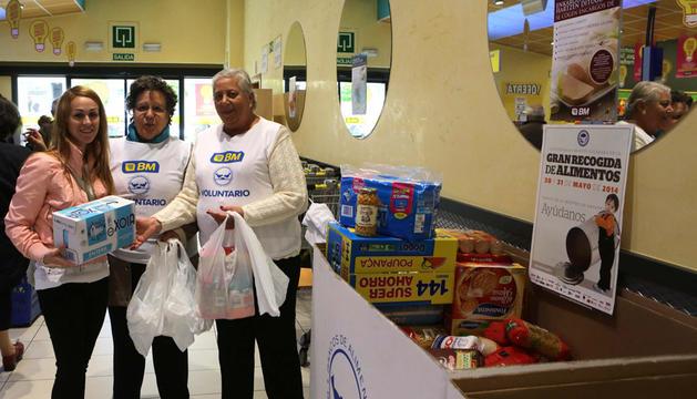 Varios voluntarios recogiendo alimentos ayer en un supermercado BM de Pamplona.
