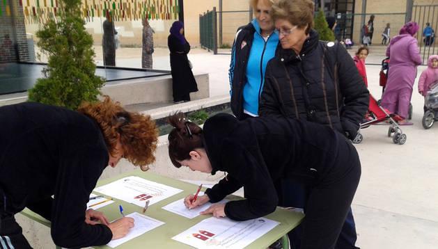 Varias personas firman a favor de la jornada continua en el colegio.