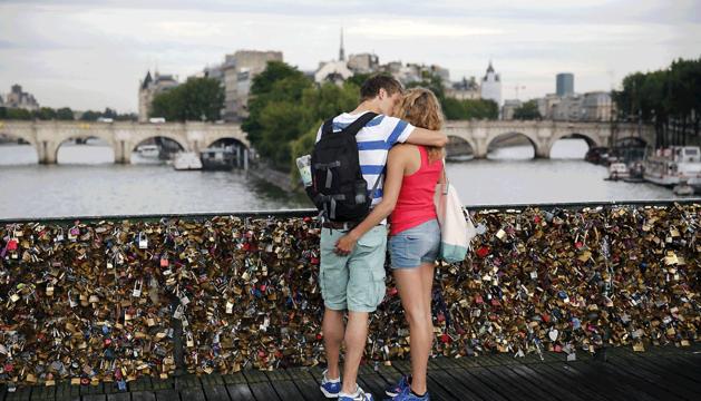 Una pareja se besa en el puente Pont des Arts, en París