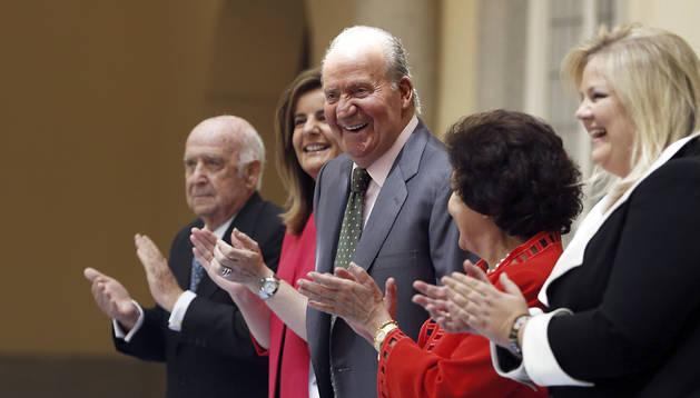 El Rey Juan Carlos, junto a la ministra de Empleo y Seguridad Social, Fátima Báñez (2ª izda.), entre otros, es aplaudido durante el acto conmemorativo del XXV aniversario de Seniors Españoles para la Cooperación Técnica
