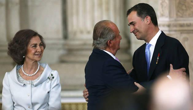 El Rey Juan Carlos besa al Príncipe de Asturias, Felipe de Borbón, junto a la Reina Sofía, tras firmar la ley orgánica por la que se hace efectiva su abdicación