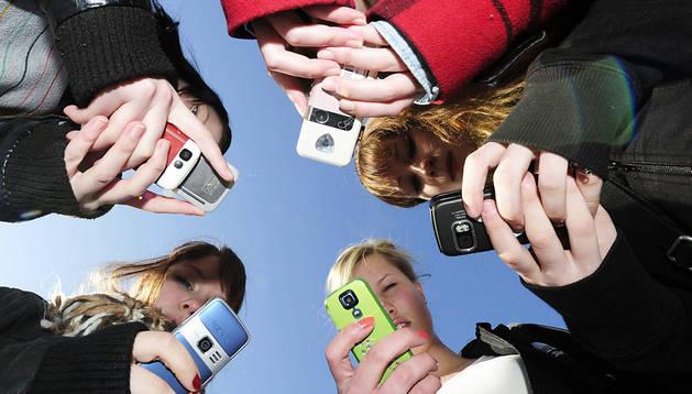 Un grupo de jóvenes reunidas mientras consultan sus teléfonos móviles