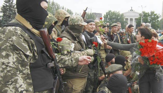 Una mujer de la localidad da rosas a los nuevos voluntarios de las fuerzas pro-ruso durante una ceremonia de juramento en la plaza central de Donetsk