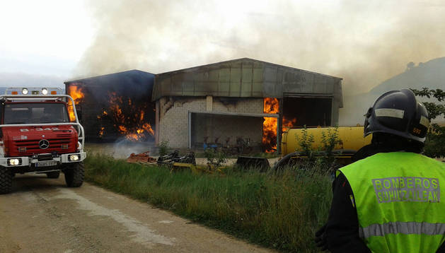 Los bomberos tratan de apagar el fuego de las naves